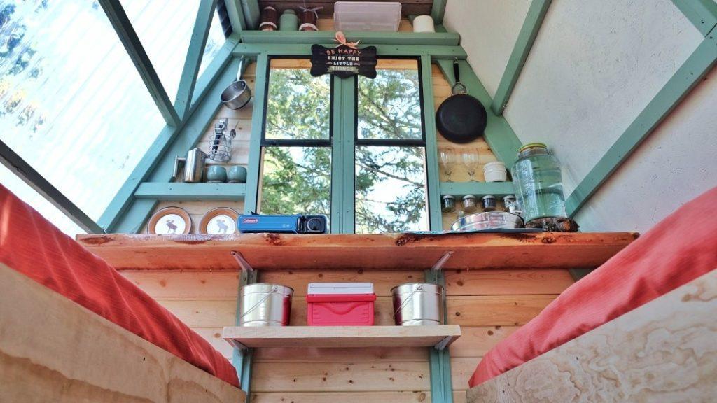 interior do chalé de madeira cozinha com camas
