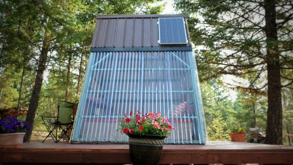lateral do chalé de madeira barato com painel solar e telha transparente