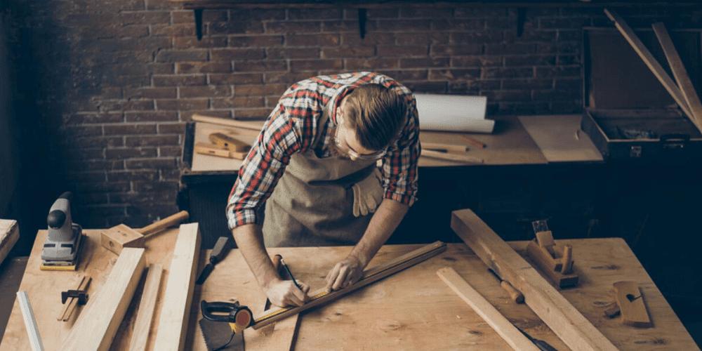 foto de marceneiro fazendo medidas em móvel de madeira