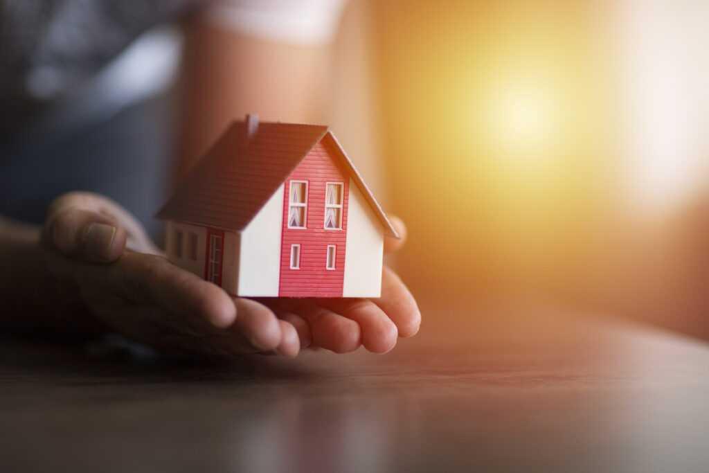 foto ilustrativa com mão segurando casa pré-fabricada em miniatura
