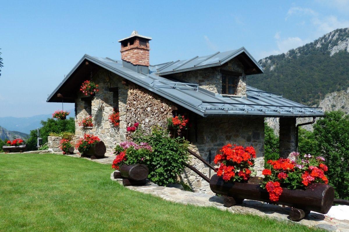 casa de campo de pedras com flores na paisagem