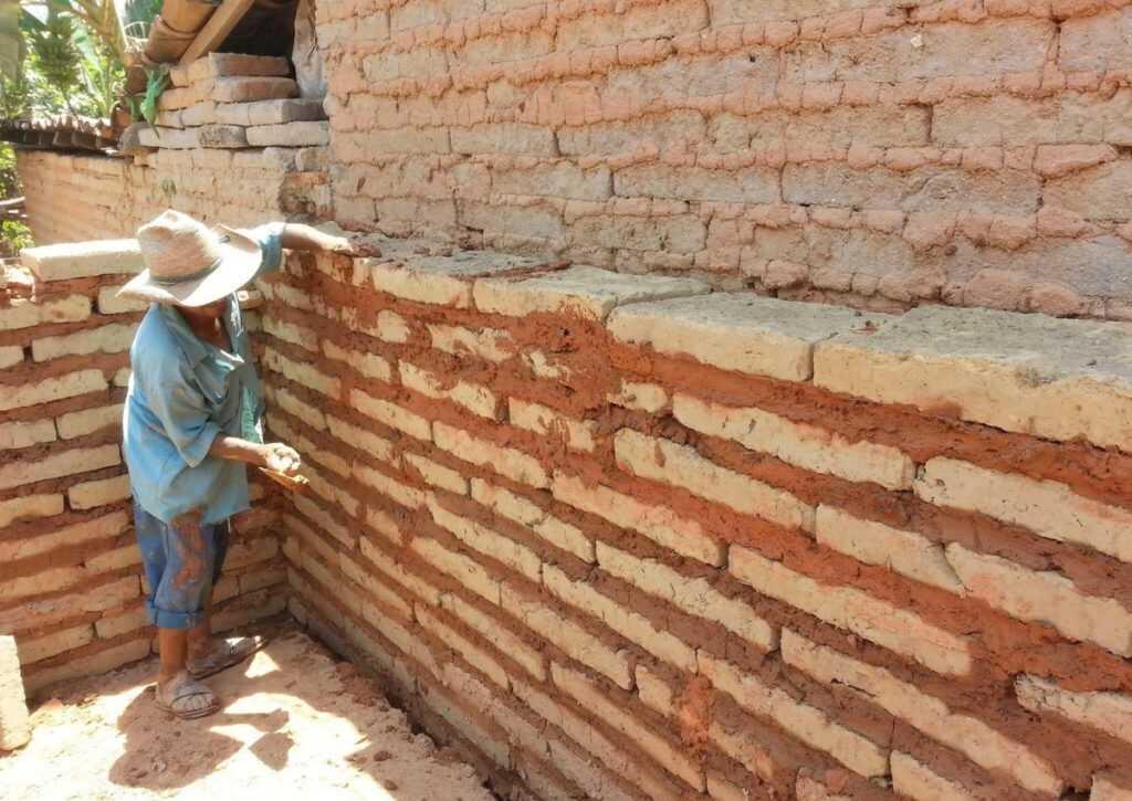 homem empilhando blocos de adobe em bioconstrução