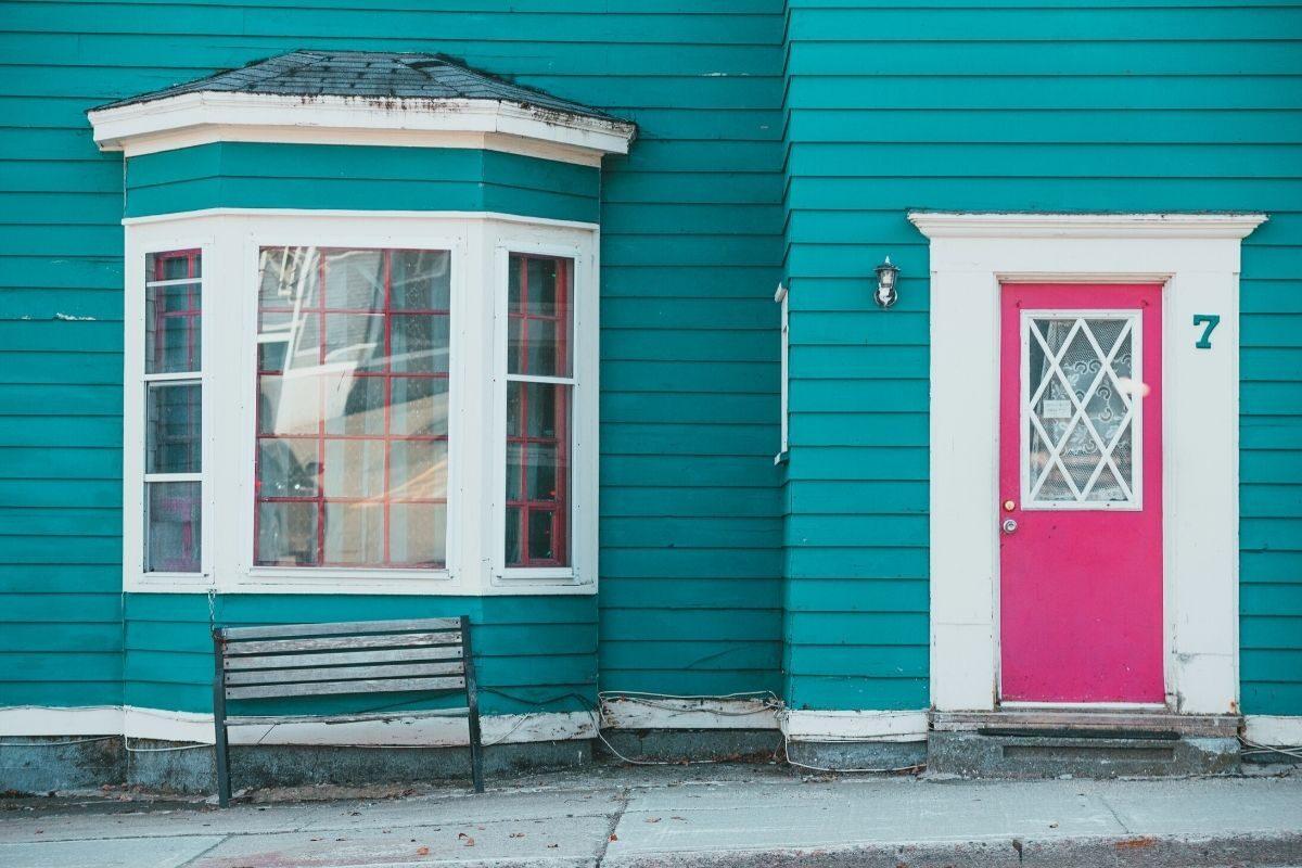 casa de madeira pintada com portas e janelas em cores diferentes