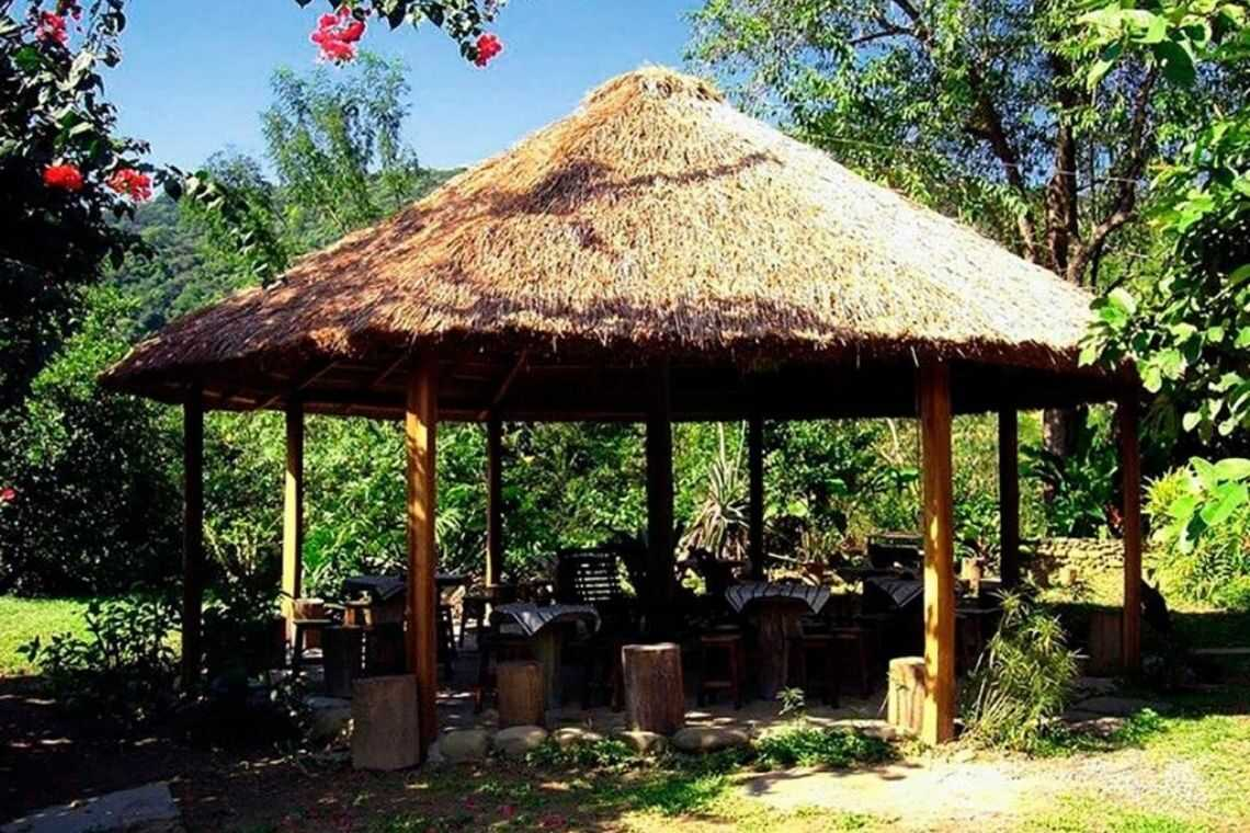 Quiosque de madeira com telhado de sapê
